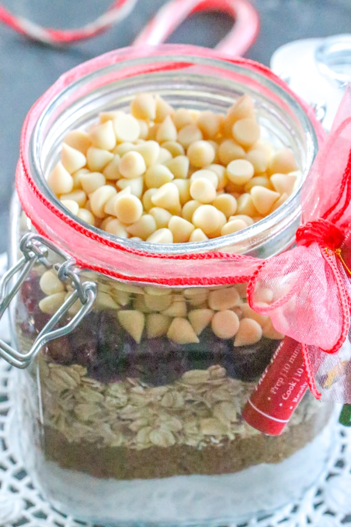 A closeup of white chocolate chips in a jar with other ingredients to make cookies