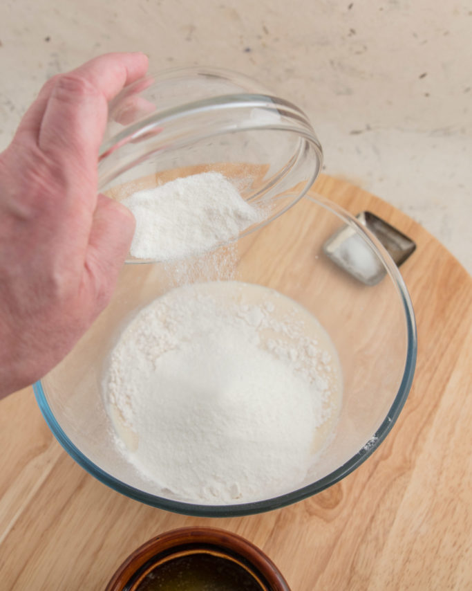 A bowl of flour with sugar being poured into it