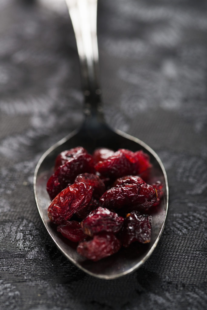 A close up of a spoonful of cranberries on a table