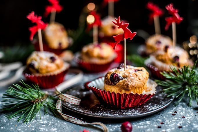 a close up side view of muffins on a gray table in red foil liners