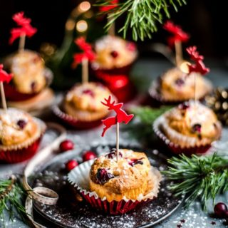 seven cranberry muffins on a gray table in red foil liners topped with red reindeer decoration