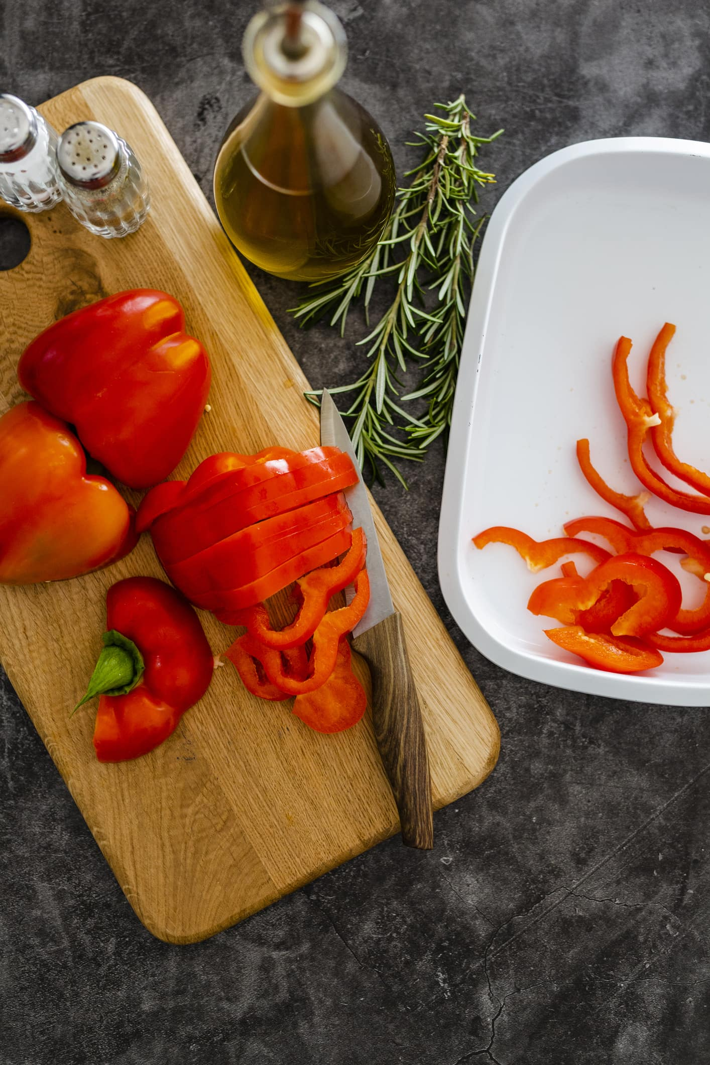 A tray of red bell pepper on a wooden cutting board