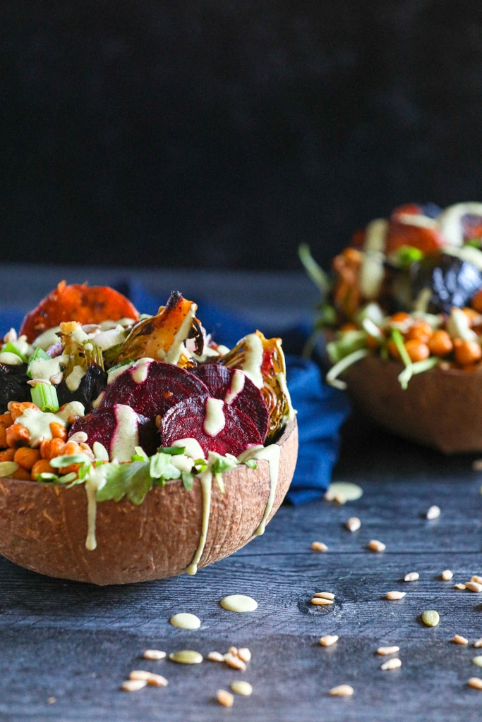 A side shot of roasted vegetables in a coconut bowl on a blue table