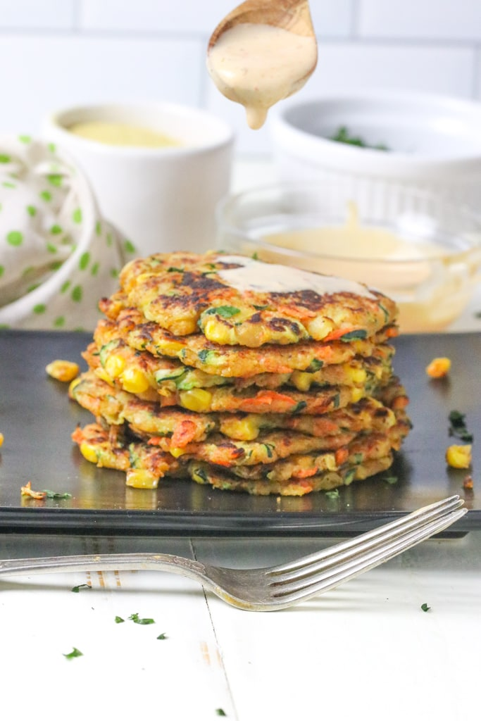A black tray on a white table with a stack of 6 fritters on it