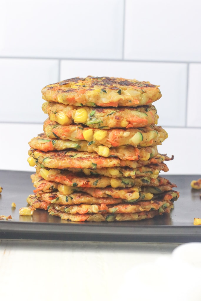 A black tray of food, with 11 fritters on it