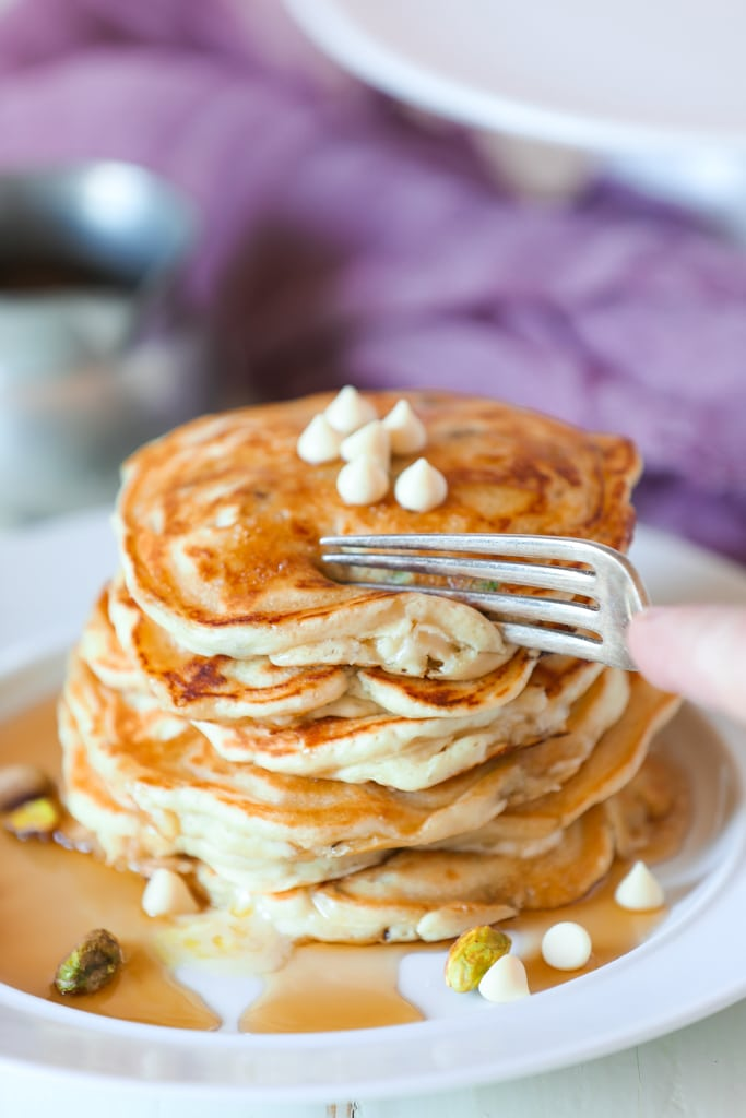 A close up of a stack of pancakes on a plate, with white chocolate chips and syrup