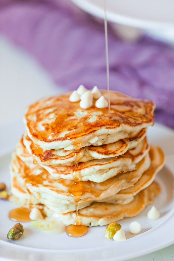 stack of vegan pancakes with syrup dripping over them