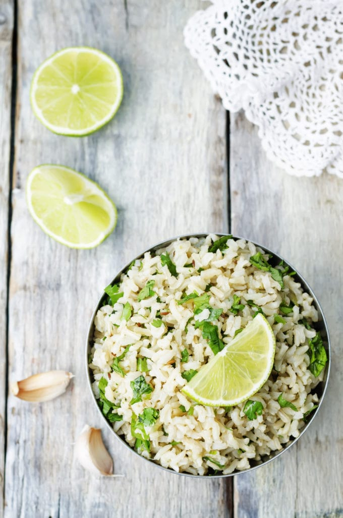 overhead shot of brown rice topped and surrounded by garlic, lime and cilantro