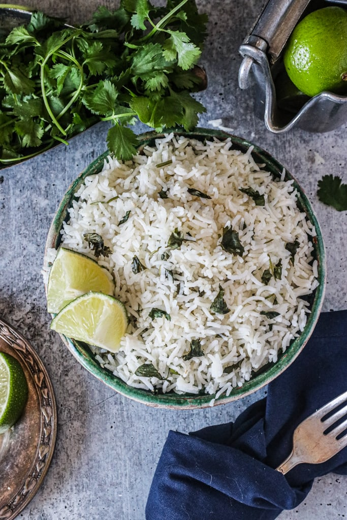 overhead shot of bowl of rice on gray table with lime and cilantro around it