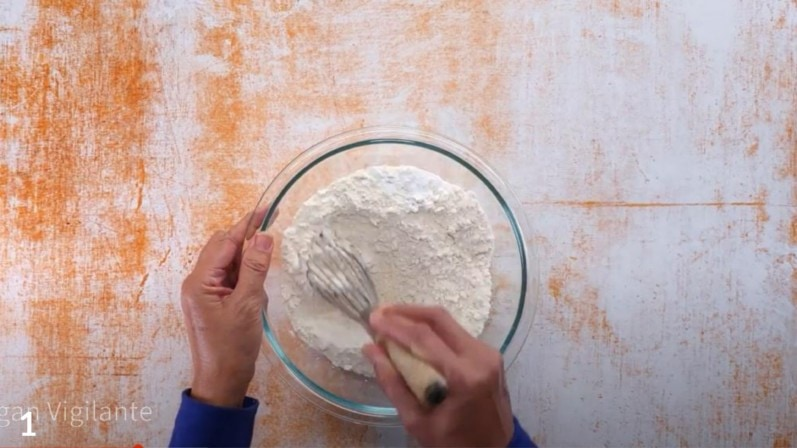 person holding a whisk in hand and mixing ingredients for naan bread