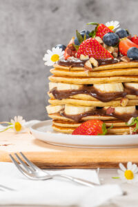 a stack of pancakes on a plate with berries, chocolate, pecans and flowers