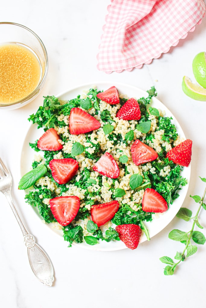 overhead shot of kale salad with strawberries on a white plate sitting on a white table