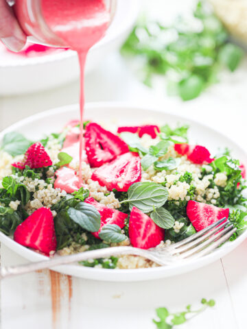 strawberry champagne vinaigrette being poured over massaged kale salad