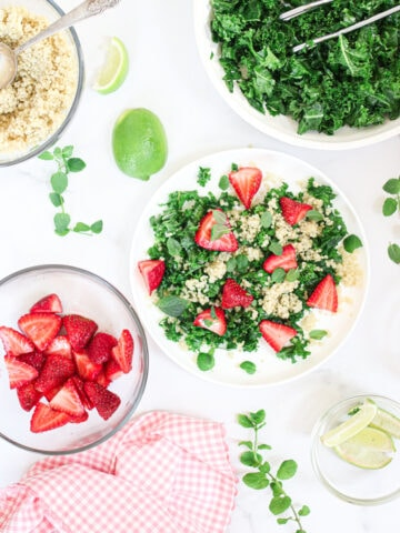 a plate of kale salad with strawberries, quinoa, kale and mint around it