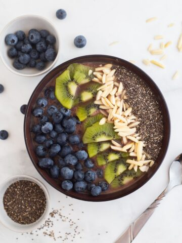 Acai smoothie bowl topped with fruit, seeds and nuts on a white table