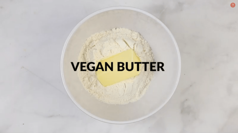 vegan butter added to bowl of flour sitting on a table