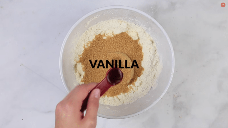 vanilla being added to a white bowl to make cookie dough