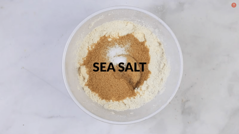 sea salt added to a white bowl on a white table