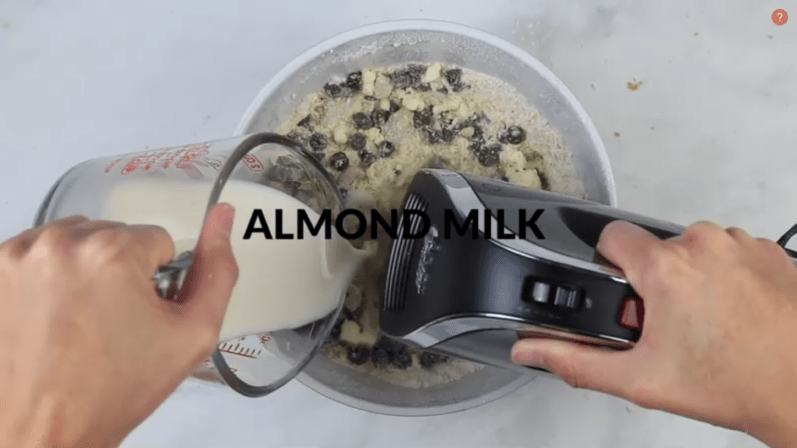 almond milk being poured into a bowl of chocolate chip cookie dough ingredients