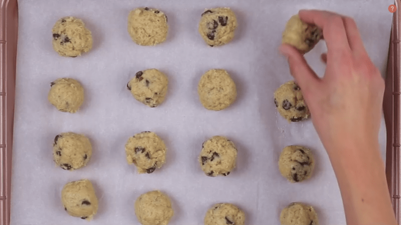 person placing last cookie dough bite on sheet pan before placing in the refrigerator