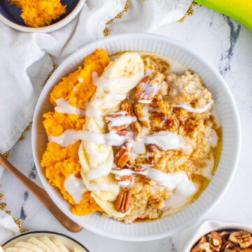 a bowl of oatmeal topped with sweet potatoes, bananas, pecans and coconut cream