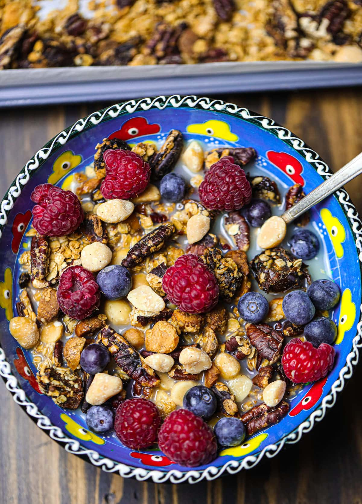 vegan granola with oat milk in a pretty decorated blue bowl on a wooden table