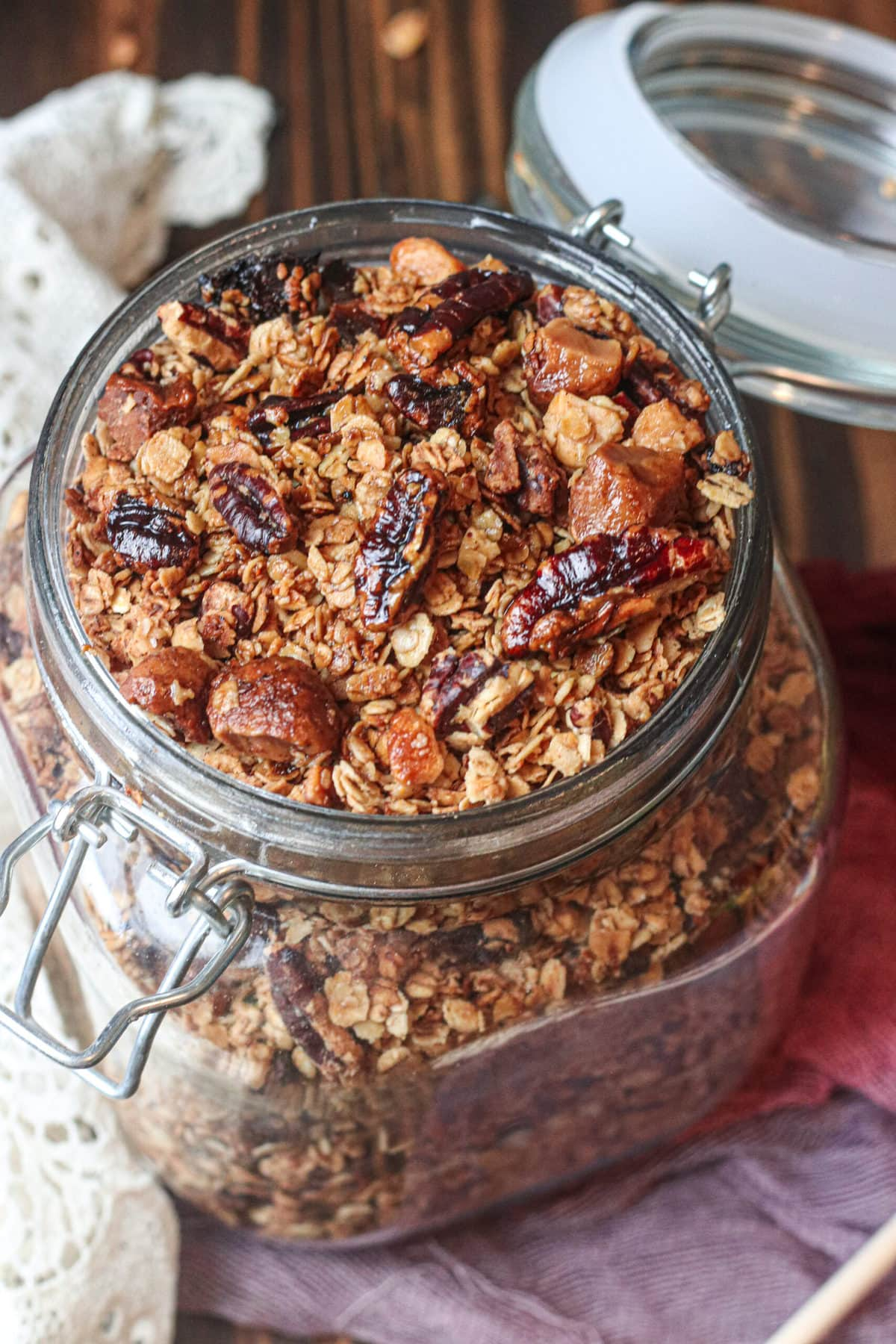 overhead shot of granola in a glass jar on a wooden table