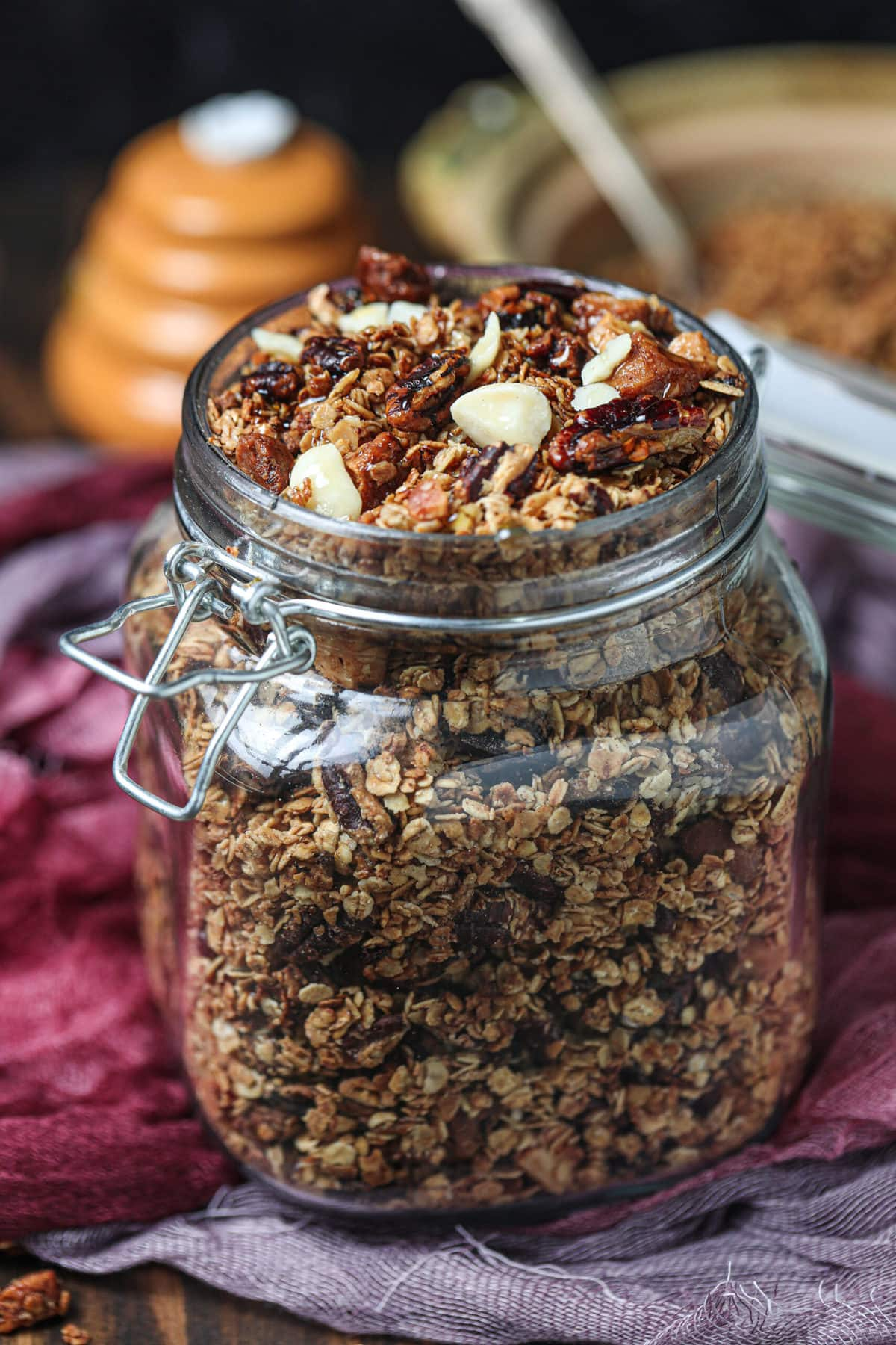 vegan granola recipe in a glass jar on a wooden table with lid open