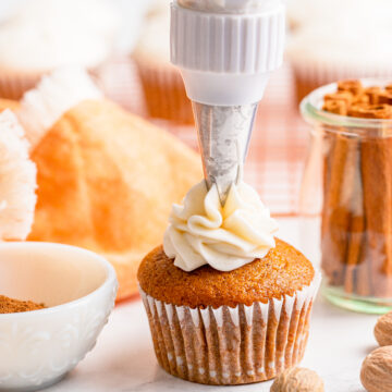 person frosting a pumpkin pie cupcake on a white table