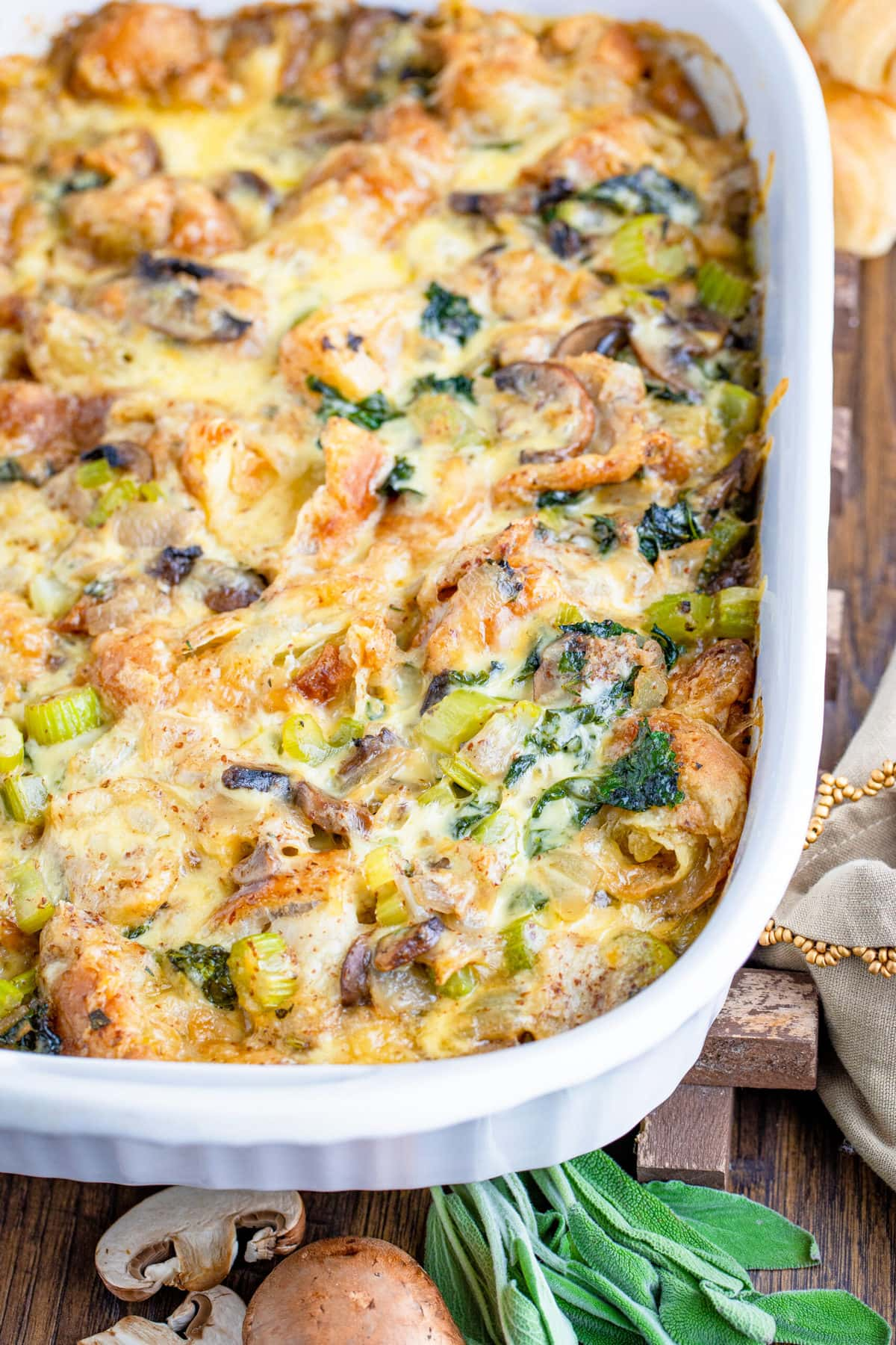 closeup of croissant stuffing recipe in white casserole dish on wooden table
