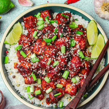 overhead shot of general tso's tofu recipe in a blue dish on an aqua background topped with garnishes