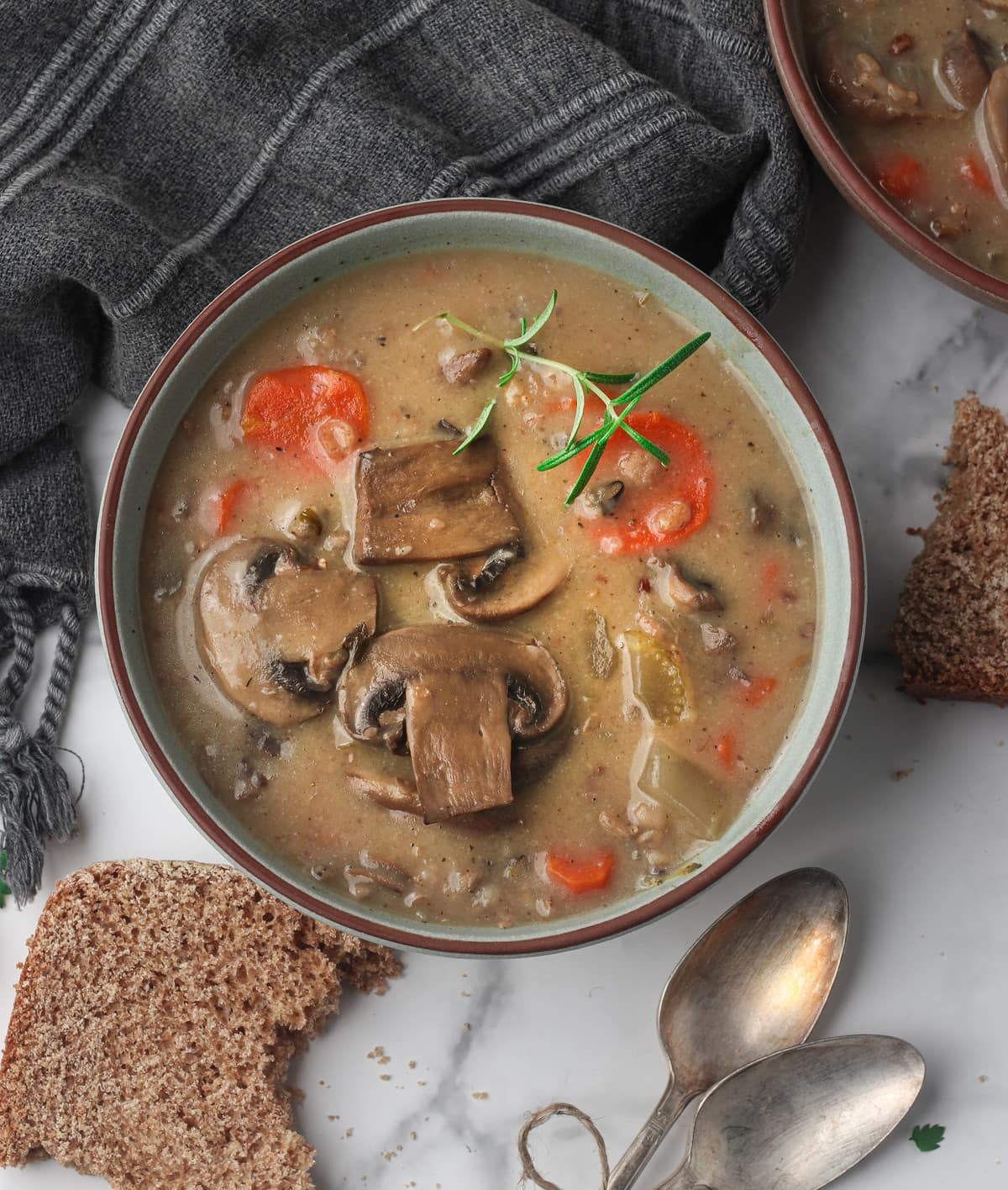 two bowls of wild rice and mushroom soup on a marble table