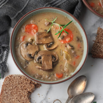 bowls of wild rice and mushroom soup on marble table