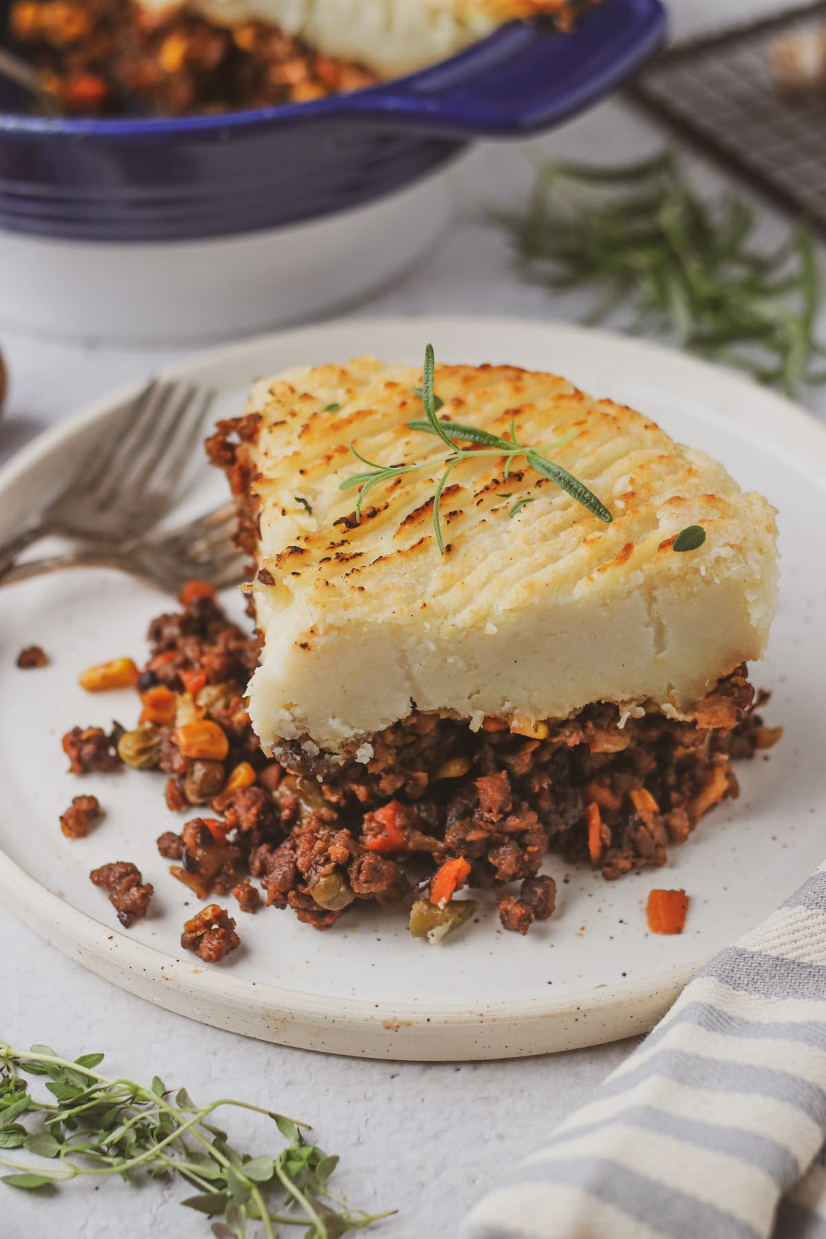 slice of vegan shepherd's pie on a white plate with remaining casserole in background