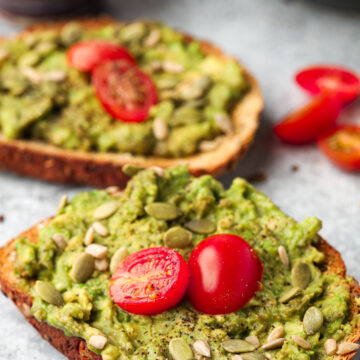 vegan avocado toast topped with cherry tomatoes on a gray table