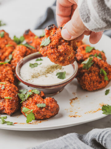 person dipping vegan cauliflower bites into dill ranch dressing