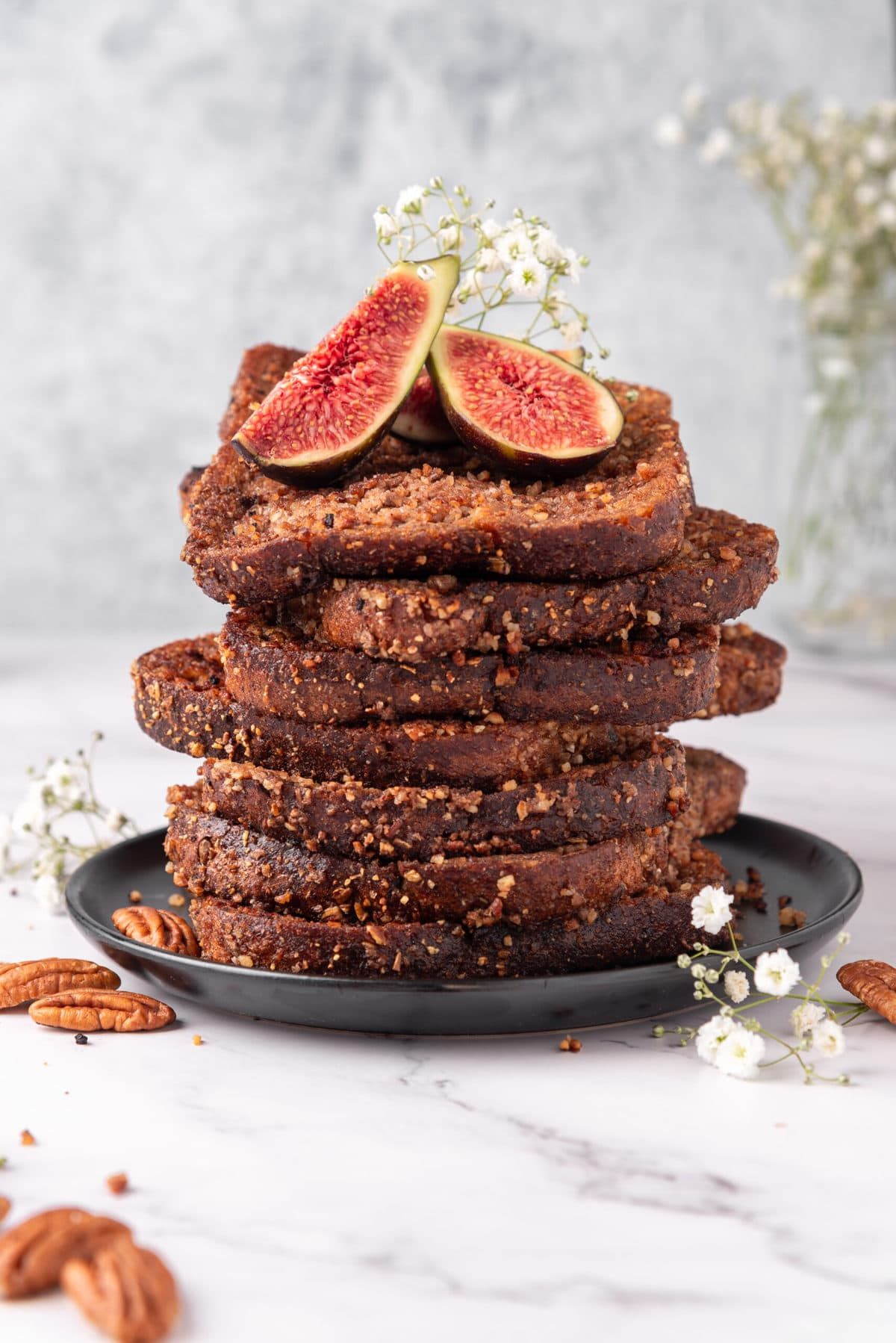 stack of vegan french toast topped with figs on a marble table